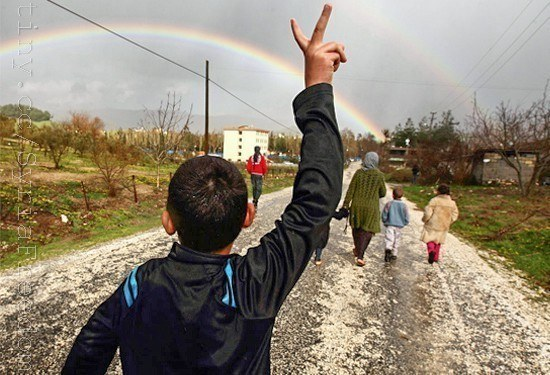 Hassan Saad, 13, who fled Idlib in Syria, flashes a victory sign while walking outside the refugees camp near the Turkish-Syrian border in the southeastern city of Yayladagi by Freedom House / Flickr